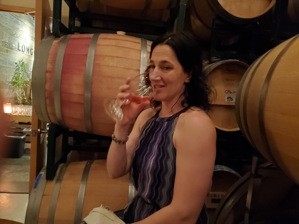 A photo of a woman enjoying a glass of wine, in front of several wine barrels.