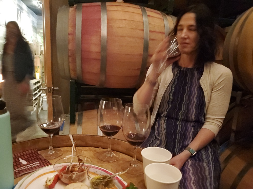 A photograph of a woman smelling a glass of wine, with a flight of glasses in front of her.
