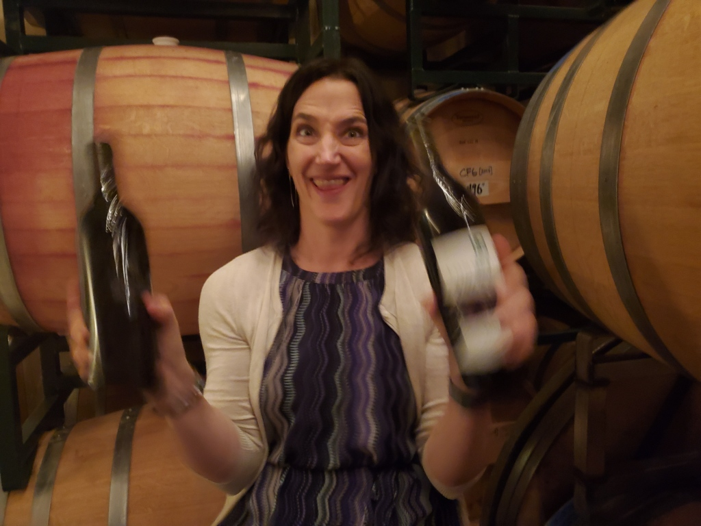 A woman with a happy grin holding 2 bottles of wine.