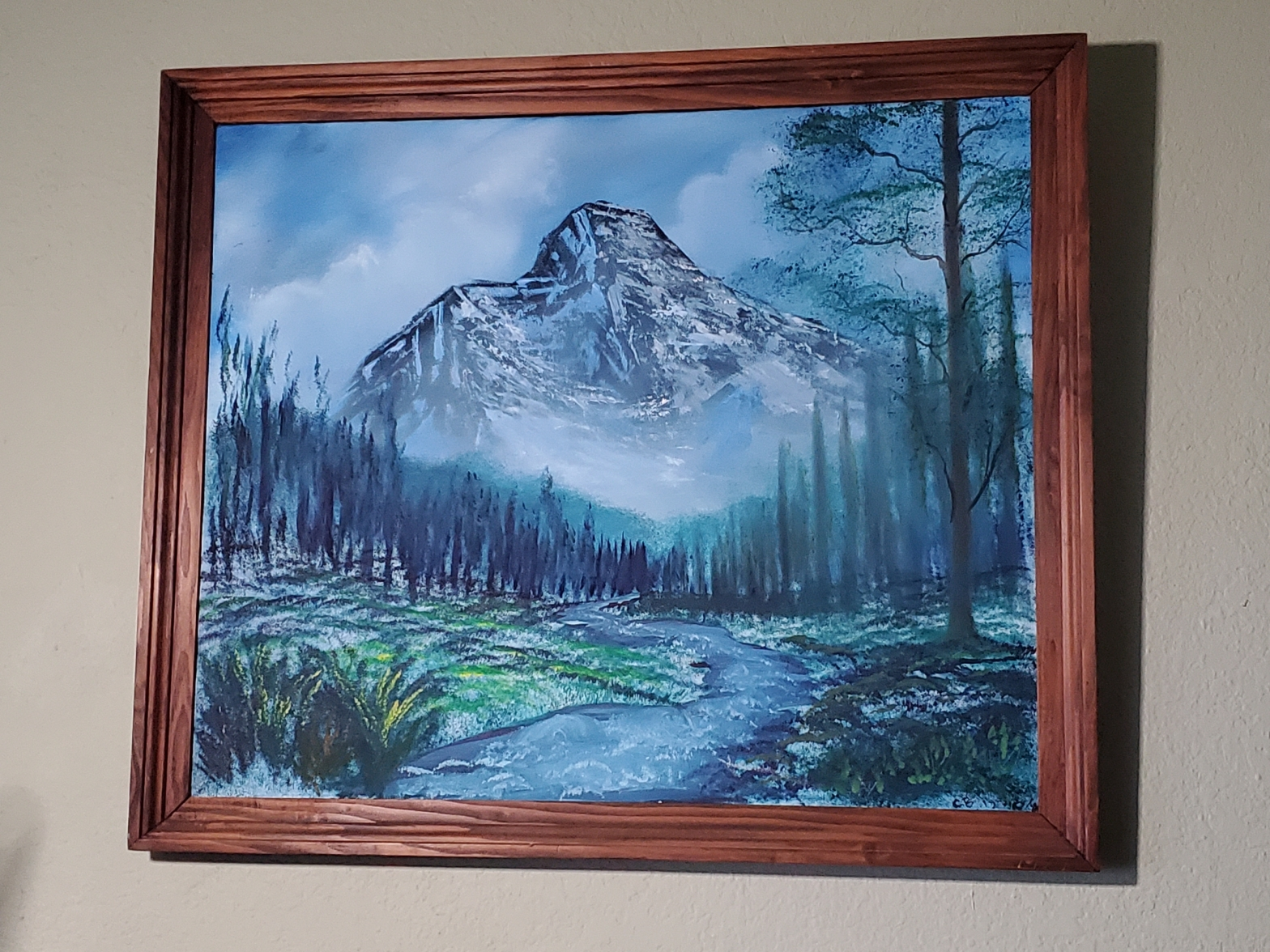An amateur painting of a mountain and a river.